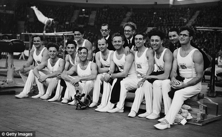 GB Men's team in the competition hall, 9 gymnasts are shown here in The Empress Hall. The three men together in spectacles are left to right, Ken Buffin, Bill King and Helmut Bantz. In front of Helmut is Arthur Whitford. Jack Whitford who broke his arm before the event so did not compete is not shown