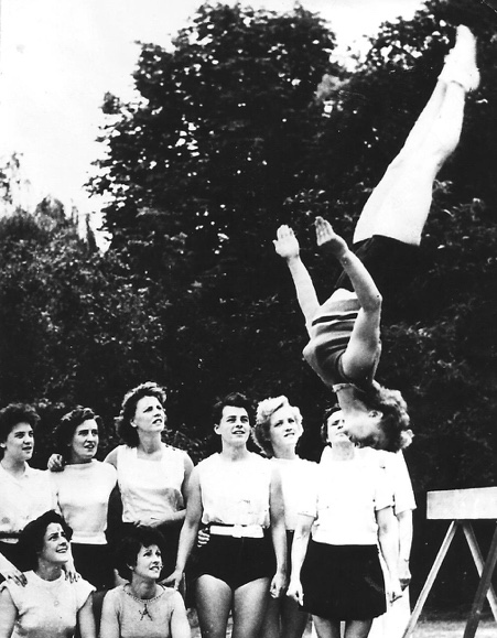 Pat Hirst demonstrating her beam dismount with team hopefuls and Carrie Pollard looking on. Once again training is outside.